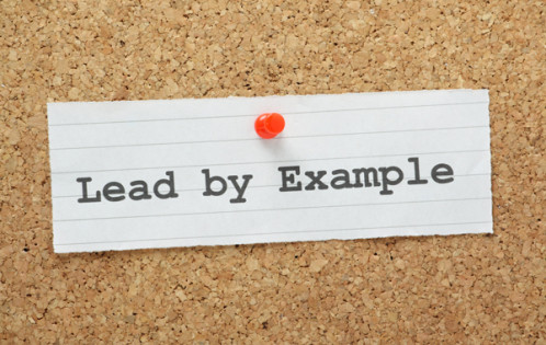 The phrase Lead By Example on a cork notice board